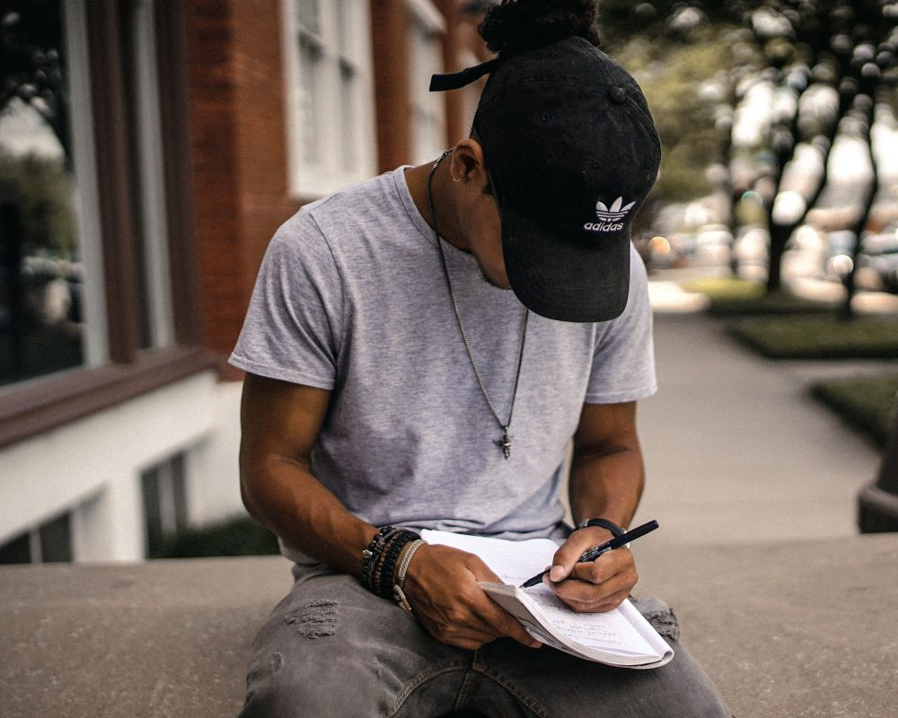 young man writing in workbook outside